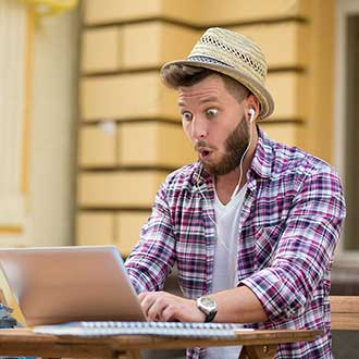 Hipster happily surprised at the computer