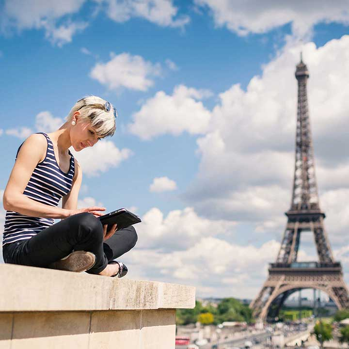 Woman with iPad sits in front of the Eiffel Tower